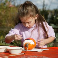 girl painting a pumpkin